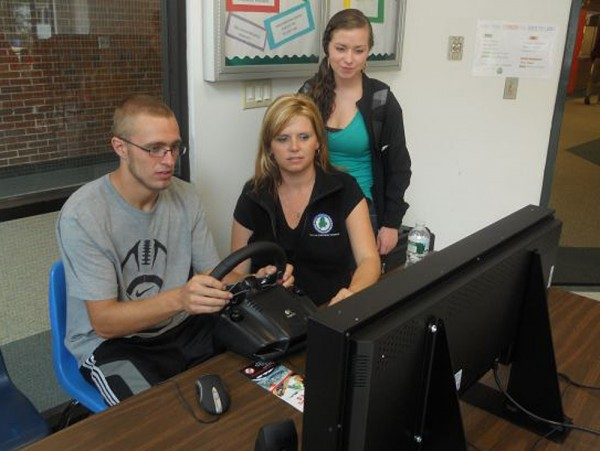 Maine Bureau of Highway Safety staffer Johannah Oberg (center) works on a driving simulator with a couple of unidentified high school students at Bonny Eagle High School recently.
