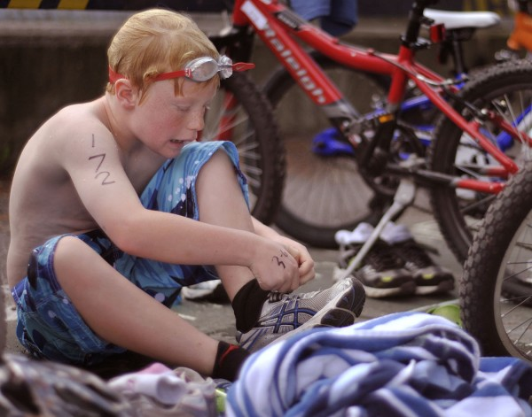 Noah Kreuz swaps out of his swim gear into his biker mode after the first part of the 6-9 year-old triathlon held at the University of Maine in Orono, Sunday Sept. 25, 2011.