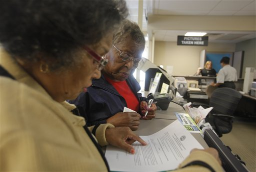 Dorothy Melvin, center, gets help from Charline Kilpatrick as she fills out a form to get a new license with her photograph on it. Several states adopted new laws last year requiring people to show a photo ID when they come to the polls to vote.