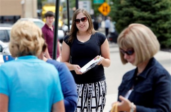 Mellissa Brown, center, a volunteer for Organizing for America, collects signatures for a petition in Columbus, Ohio, in a ballot repeal effort by opponents of the Ohio's new elections law. After years of expanding when and how people can vote, state legislatures now under new Republican control are moving to trim early voting days, beef up identification requirements and put new restrictions on how voters are notified about absentee ballots.