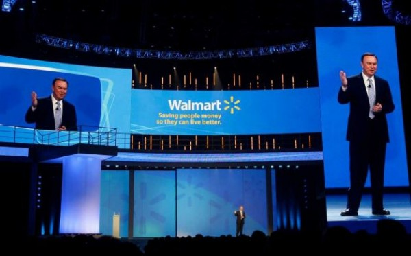 Mike Duke, president and CEO of Wal-Mart, speaks to shareholders as his image appears on screens left and right in Fayetteville, Ark., last spring. Wal-Mart is investing in new technologies to expand shopping.