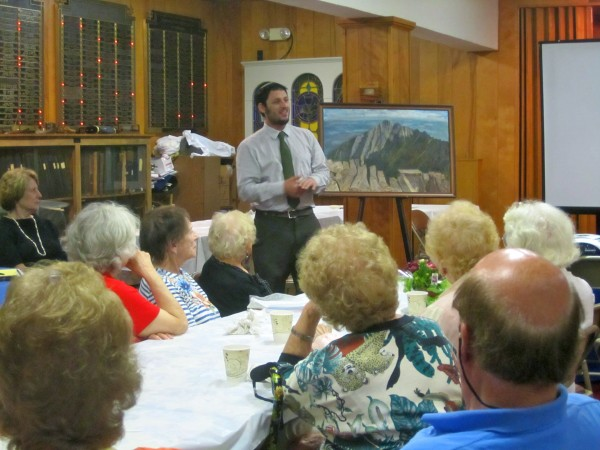 Rabbi Justin Goldstein gives a talk about his first ascent of Mt. Katahdin at a meeting of Temple Beth Israel's Friendship Club.  In the background is an original painting of Mt. Katahdin by Friendship Club member, Norman Stern.