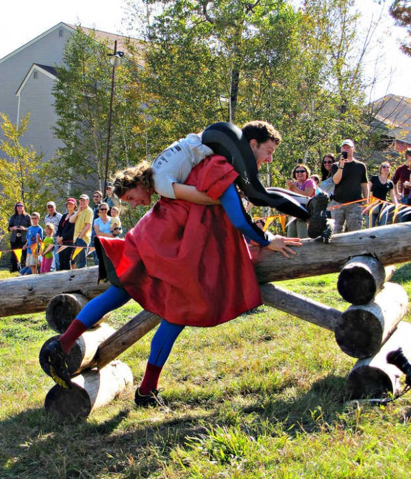John Lund, aka Super Husband, flies over a log hurdle carrying a woman he met at Sunday River's 12th annual North American Wife Carrying Championship. Lund was at the event to promote the 2012 World Alternative Games being held in the United Kingdom in Wales. The World Alternative Games also includes a wife-carrying competition.