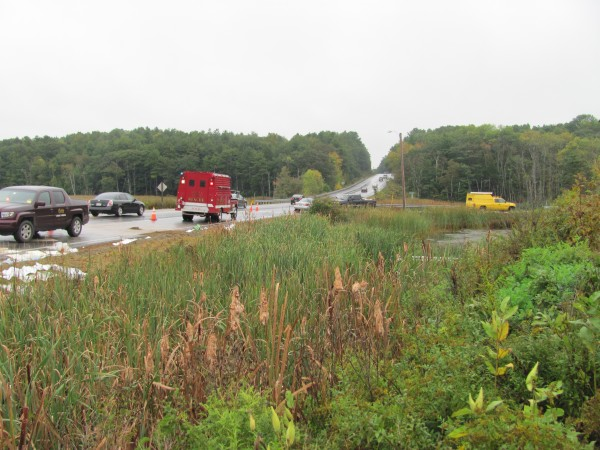 Rescue crews and workers from Clean Harbors Chemical of South Portland try to contain gasoline, transmission fluid and hydraulic fluid that spilled on Saturday, October 1, 2011 on Route 1 in Woolwich when the drivetrain in a large mobile crane malfunctioned. The clean-up effort is expected to last several days.