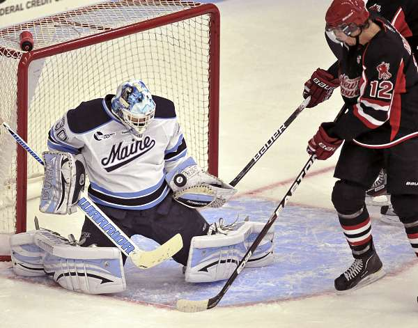Maine goalie Dan Sullivan (30) makes a glove save on New Brunswick forward Nick MacNeil (12) in the first period of their game in Orono Sunday, Oct. 3, 2011.