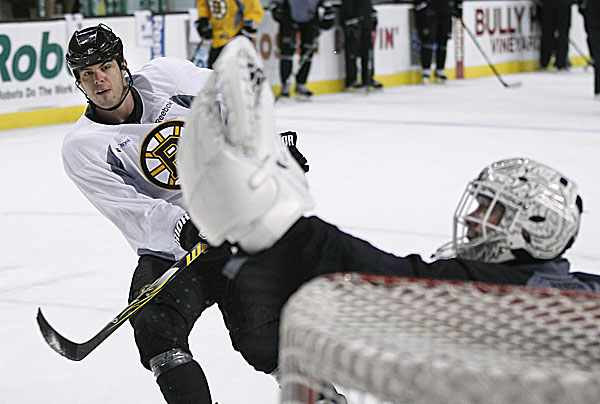 Tim Thomas of the Boston Bruins makes a save on teammate Nathan Horton during Wednesday's practice at the TD Garden in Boston. The Stanley Cup champions open the season Thursday against Philadelphia and will raise the championship banner.