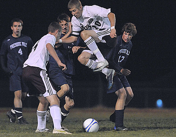 Kyle Haslam (10) of Ellsworth jumps to give teammate David Barnard (front left) a shot at the ball under pressure from Presque Isle's Cole Richards (back center) and Colin McKay (right) in the second half of their game in Ellsworth Wednesday. The host Eagles won 4-1.
