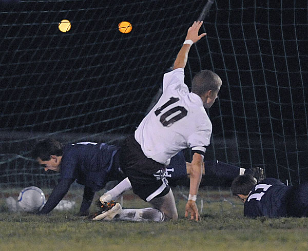 Ellsworth's Kyle Haslam (10) signals a score as he kicks the ball past Presque Isle's Logan Good (4) and Cole Richards (11) in the second half of Wednesday's boys soccer game in Ellsworth. Ellsworth won 4-1.