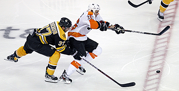 Boston Bruins center Patrice Bergeron, left, tries to chase down Philadelphia Flyers center Zac Rinaldo during the second period of an NHL game in Boston, Thursday night, Oct. 6, 2011.