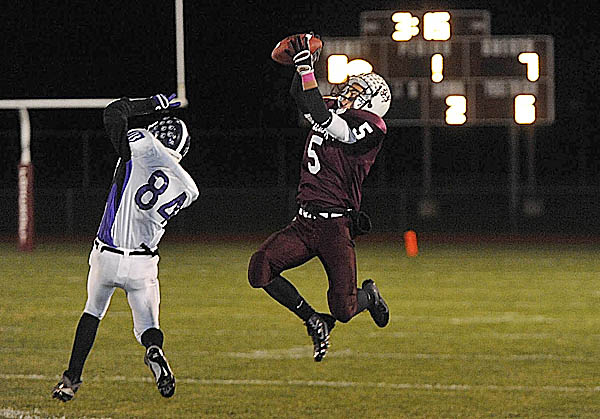 Foxcroft Academy wide receiver Ryan Rebar goes airborne to catch a pass over John Bapst Memorial High School's Josh Baker during Friday night's game in Dover-Foxcroft.