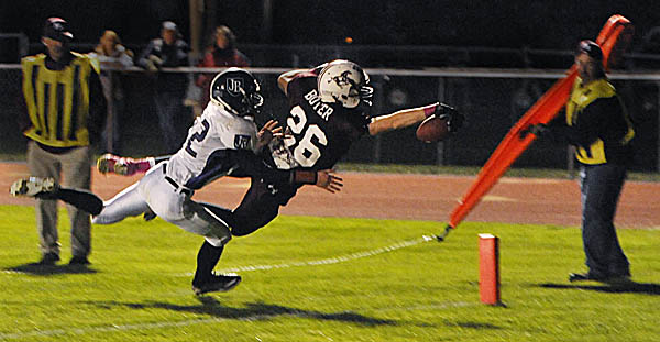 Foxcroft Academy's Don Boyer (26) dives into the end zone with John Bapst Memorial High School's Andrew Catlin in pursuit during the first quarter of Friday night's game in Dover-Foxcroft.