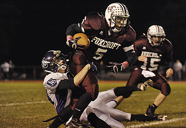 Foxcroft Academy wide receiver Ryan Rebar (5) is slowed by John Bapst Memorial High School's Josh Baker on a carry at the start of the first quarter of Friday night's game in Dover-Foxcroft.