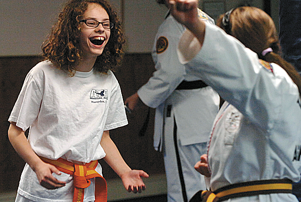 Didi Bryant laughs as she practices at Hampden ATA Martial Arts recently. Owned by Marjorie Earl and featuring an all-female staff, the school attracts many members of both sexes interested in a family- and community-based setup.