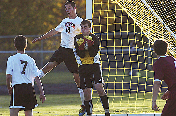 Bangor High School goalkeeper Liam Herrigan makes a save as Brewer High School's Nick Ramsey (18) and Zack Gulesian apply pressure at the end of the second half of their match in Brewer Tuesday afternoon, Oct. 11, 2011. Bangor defeated Brewer 1-0.