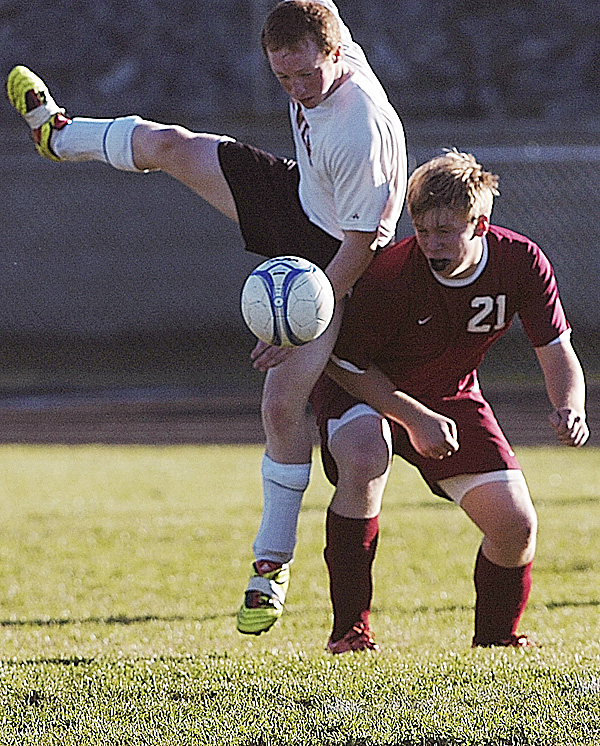 Brewer High School's Chris Worden, left,  and Bangor High School's Hunter Boyce (21) converge on the ball during the first half of their match in Brewer Tuesday afternoon, Oct. 11, 2011. Bangor defeated Brewer 1-0.