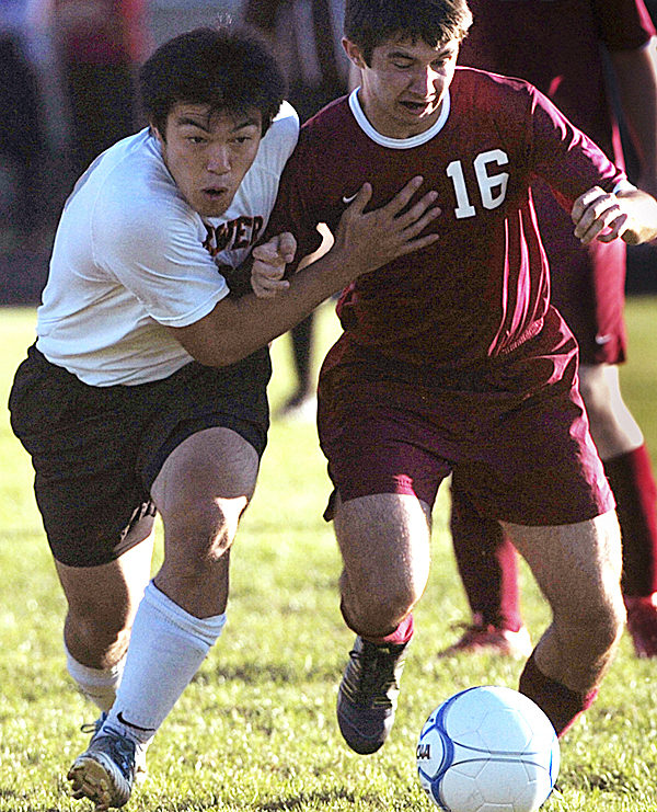 Brewer High School's Yuhi Sasaki, left, and Bangor High School's Bobby Reasso muscle each other as they go after the ball in the first half of their match in Brewer Tuesday afternoon, Oct. 11, 2011. Bangor defeated Brewer 1-0.
