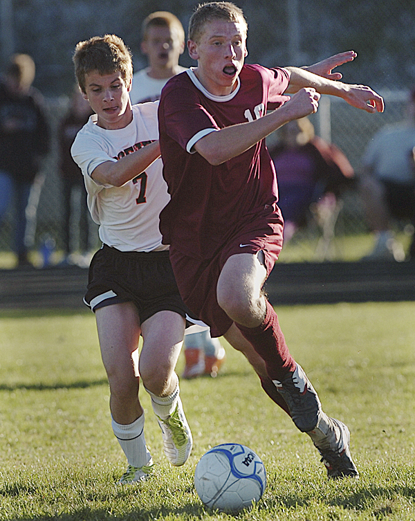 Brewer High School's Zack Gulesian (7) and Bangor High School's John Szewczyk run down a loose ball in the the second half of their match in Brewer Tuesday afternoon, Oct. 11, 2011. Bangor defeated Brewer 1-0.