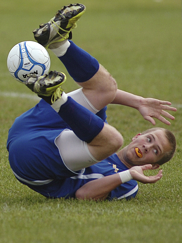 Hermon High School's Kevin Frederick tumbles after colliding with Old Town High School's Tyler Lynch (not pictured) in first-half soccer action at in Old Town Wednesday afternoon, Oct. 12, 2011.