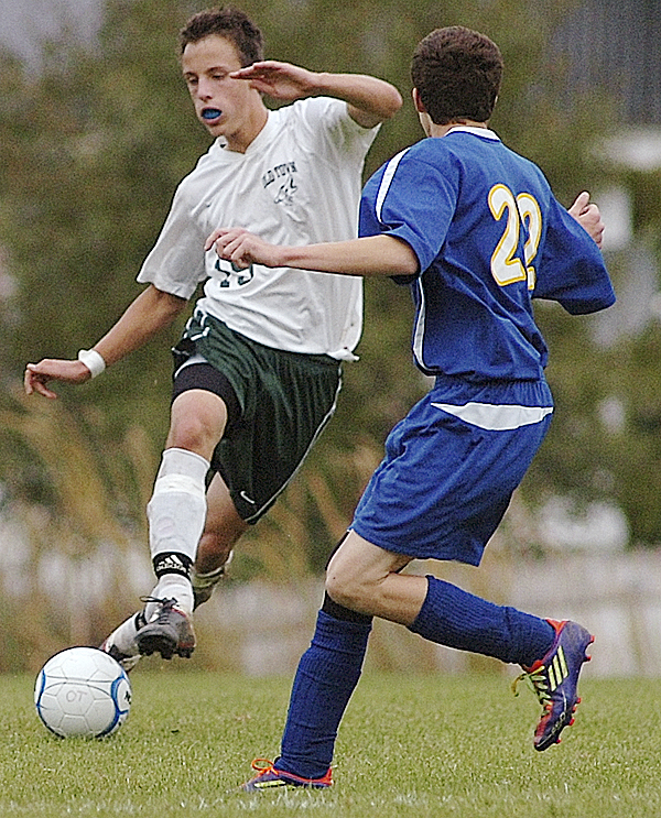 Old Town High School's Thorbin Trebing, left, maneuvers near Hermon High School's Matthew Cullens during  first-half soccer action in Old Town Wednesday afternoon, Oct. 12, 2011.