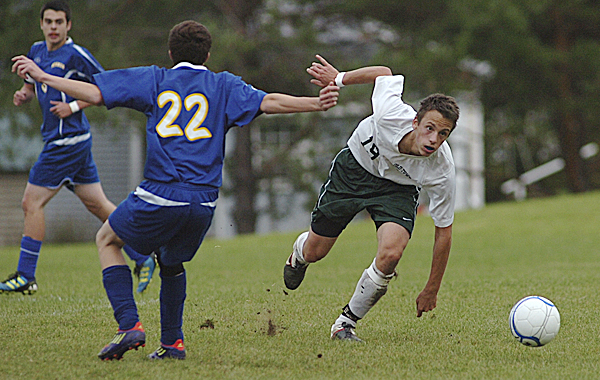 Old Town High School's Thorbin Trebing, right, accelerates to the ball as Hermon High School's Matthew Cullens (22) approaches during first-half soccer action in Old Town Wednesday afternoon, Oct. 12, 2011.