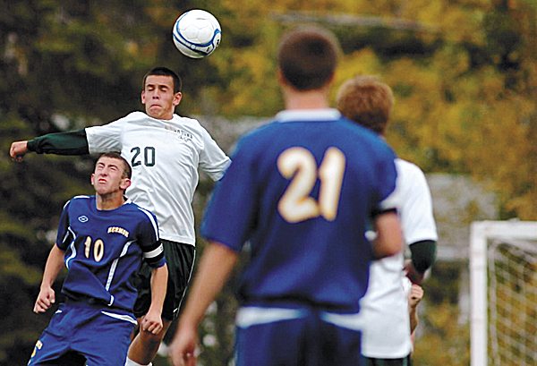 Old Town High School's Gabe Melmed (20) heads a ball with pressure from Hermon High School's Dylan Smith (10) during first-half soccer action in Old Town Wednesday afternoon, Oct. 12, 2011. In the foreground is Hermon High School's Braddock Deabay.
