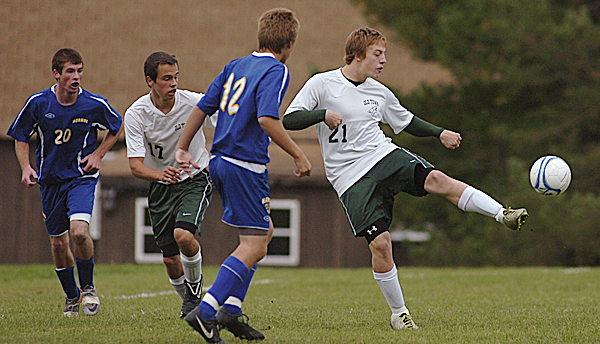Old Town High School's David Wilcox kick the ball to a teammate in first-half soccer action at Old Town Wednesday afternoon, Oct. 12, 2011. Nearby are Hermon's Brady Knowles (20), Old Town's Drew Van Steenberghe (17) and Hermon's Jacob Applebee (12).