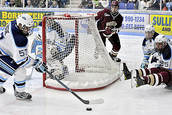 Maine's Matt Mangene (57) clears the puck from behind the net during a game last season against Boston College. Mangene has made a smooth transition to defense for the Black Bears.