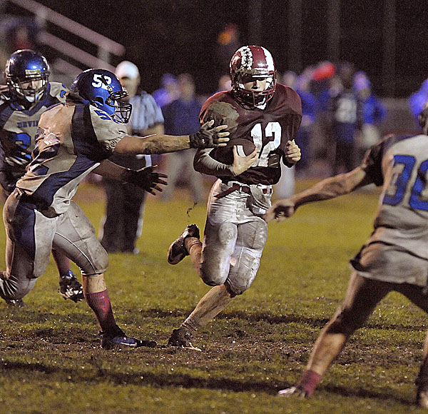 Bangor QB Carl Farnham (12) calls  his own number on a play in the second quarter of their game and tries to get by Lewiston's Mike Nazaroff (52) Friday Oct. 14, 2011.