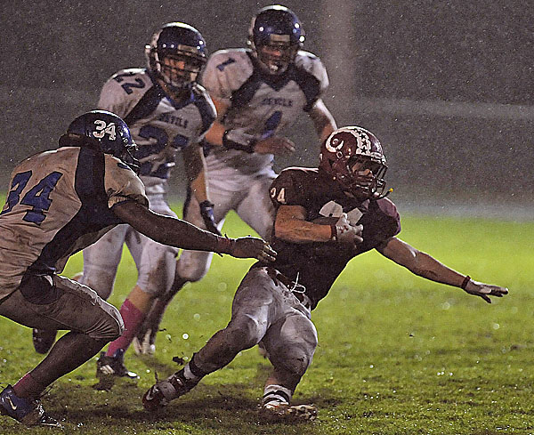 Bangor's Zeb Tuell (24) loses his footing under pressure from Lewiston's Jeff Turcotte (34) in the first quarter of their game in Bangor Friday Oct. 14, 2011.