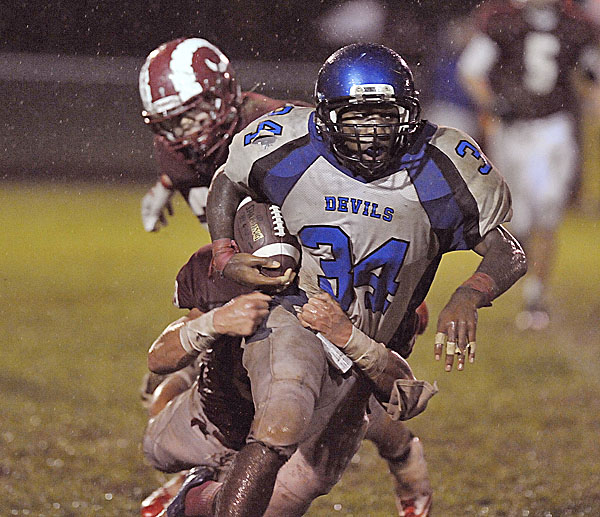 Lewiston running back Jeff Turcotte (34) gets hauled down from behind by Bangor's Cody Chapman in the first half of their game in Bangor Friday Oct. 14, 2011.