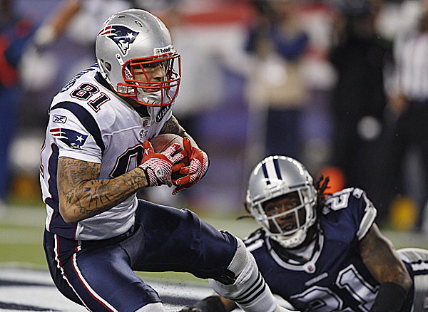 New England Patriots tight end Aaron Hernandez (81)  catches a touchdown pass as Dallas Cowboys cornerback Mike Jenkins (21) watches late in the fourth quarter of an NFL football game in Foxborough, Mass., Sunday, Oct. 16, 2011. The Patriots defeated the Cowboys 20-16.