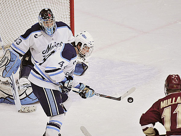 Maine defenseman Ryan Hegarty uses his stick to stop a puck in front of goalie Shawn Sirman while Boston College's Pat Mullane looks on during a game last season. Hegarty has been moved to the net front on the University of Maine hockey team's power play.