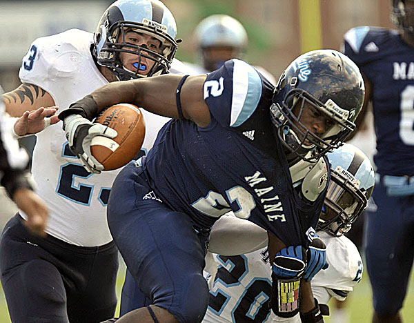 Maine running back Pushaun Brown is pulled down by Rhode Island's Michael Okunfolmi (20) and Doug Johnson during the first half of Saturday's game at Alfond Stadium in Orono. Maine improved to 5-1 with a 27-21 victory.