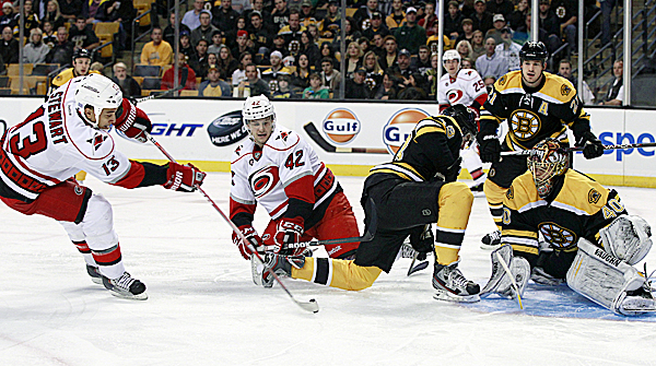 Carolina Hurricanes right wing Anthony Stewart (13) swoops in to shoot and score against Boston Bruins goalie Tuukka Rask (40) as teammates center Brett Sutter (42) and defenseman Joni Pitkanen (25) look on. Boston Bruins defenseman Matt Bartkowski (43) and defenseman Andrew Ference (21) try to defend in the first period in Boston Tuesday  night, Oct. 18, 2011.