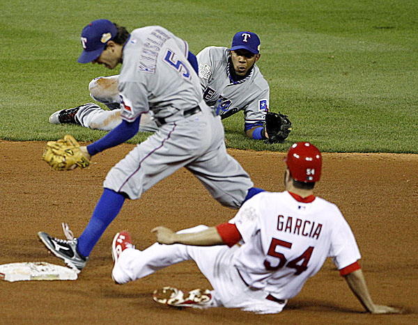 Texas Rangers' Elvis Andrus watches after flipping the ball to Ian Kinsler (5) and forcing out St. Louis Cardinals' Jaime Garcia (54) on a ball hit by Rafael Furcal during the fifth inning of Game 2 of the World Series Thursday night, Oct. 20, 2011, in St. Louis. The Rangers went on to post a 2-1 victory.