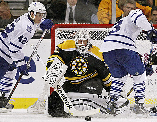 Boston Bruins goalie Tim Thomas, center, makes a save on a shot by Toronto Maple Leafs center Nazem Kadri, right, in the second period of an NHL hockey game in Boston, Thursday, Oct. 20, 2011. At left is Leafs center Tyler Bozak.