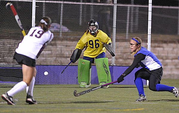 Nokomis' Leah Edmonson (19) hits the ball slightly wide of the post as Belfast goalkeeper Julia Ward and Brittany Mellor (right) defend during the first half of their Eastern Maine Class B field hockey final in Hampden Tuesday evening.