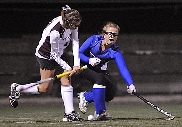 Nokomis' Leah Edmonson, left, and Kristi Osgood go after the ball in the first half of their Eastern Maine Class B field hockey championship in Hampden Tuesday evening, Oct. 25, 2011.