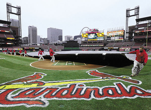 Workers pull the tarp over the field at Busch Stadium in St. Louis after Game 6 of the World Series between the Cardinals and the Texas Rangers was postponed due to a forecast of heavy rain. The game will be held Thursday with Game 7 on Friday.