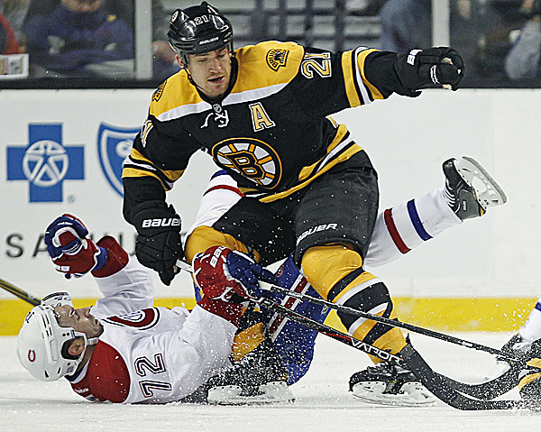 Boston Bruins defenseman Andrew Ference, top, drops Montreal Canadiens left wing Erik Cole to the ice on a hard check in the second period of an NHL game in Boston,Thursday, Oct. 27, 2011.