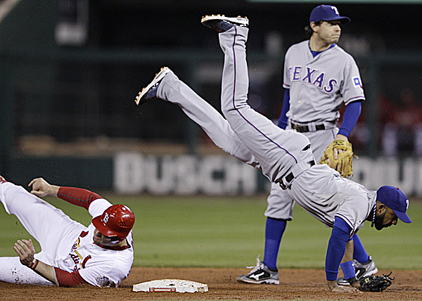 Texas Rangers' Elvis Andrus flips over St. Louis Cardinals' Matt Holliday (7) as he tries to throw out David Freese during the fourth inning of Game 6 of the World Series Thursday night, Oct. 27, 2011, in St. Louis. Freese beat the throw. The Cards went on to win 10-9 in the 11th on a Freese solo home run.