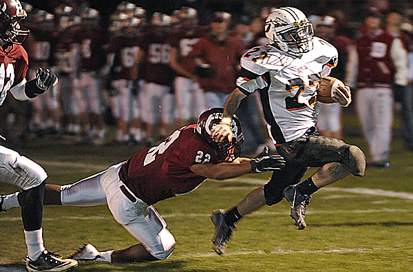 Skowhegan runningback Adam Dusty runs in the game's first touchdown with Bangor defensive back Xavier Lewis hanging on during the first quarter Friday night at Cameron Stadium in Bangor.