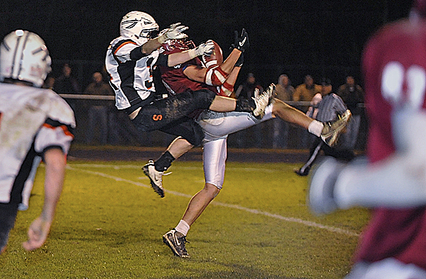 Bangor captain Ellis Throckmorton catches a touchdown pass with Skowhegan's Chad Carroll defending with 2:30 left in the second quarter Friday night at Cameron Stadium in Bangor.