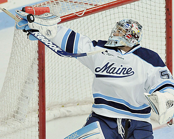 UMaine goalie Martin Ouellette (51) gets a blocker pad on a puck just high of the goal in the first period of their game against Providence in Orono Friday, Oct. 28, 2011.