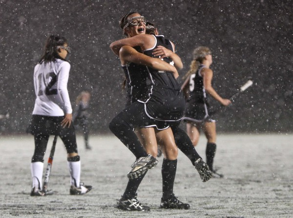 Skowhegan field hockey players Makaela Michonski, (facing camera) embraces teammate Jessica Skillings after their team defeated Marshwood in the snow for the state championship, in Yarmouth on Saturday, Oct. 29, 2011.