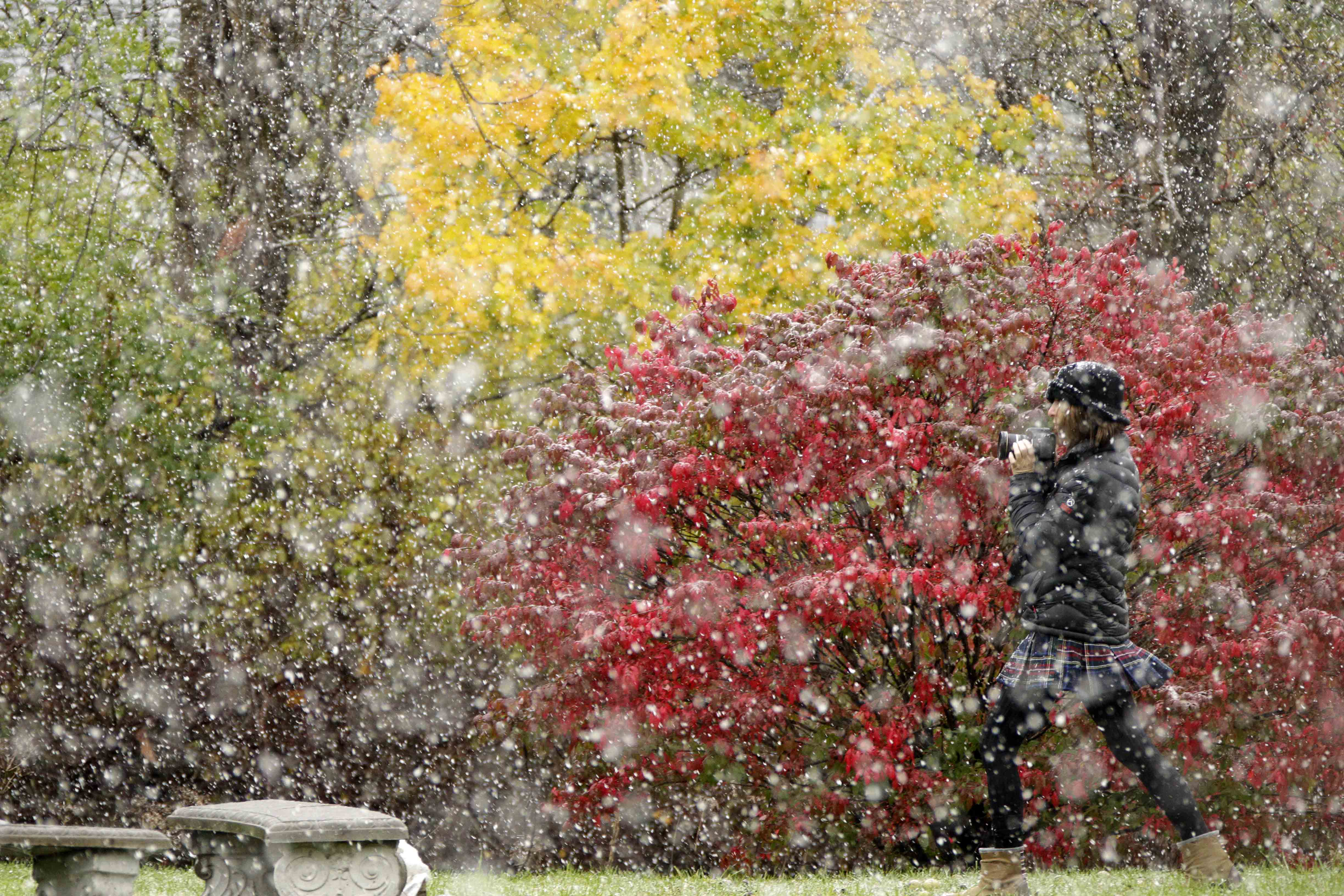 Jill Shapiro takes photographs of the falling snow at a park in Bellefonte, Pa., Saturday, Oct. 29, 2011.