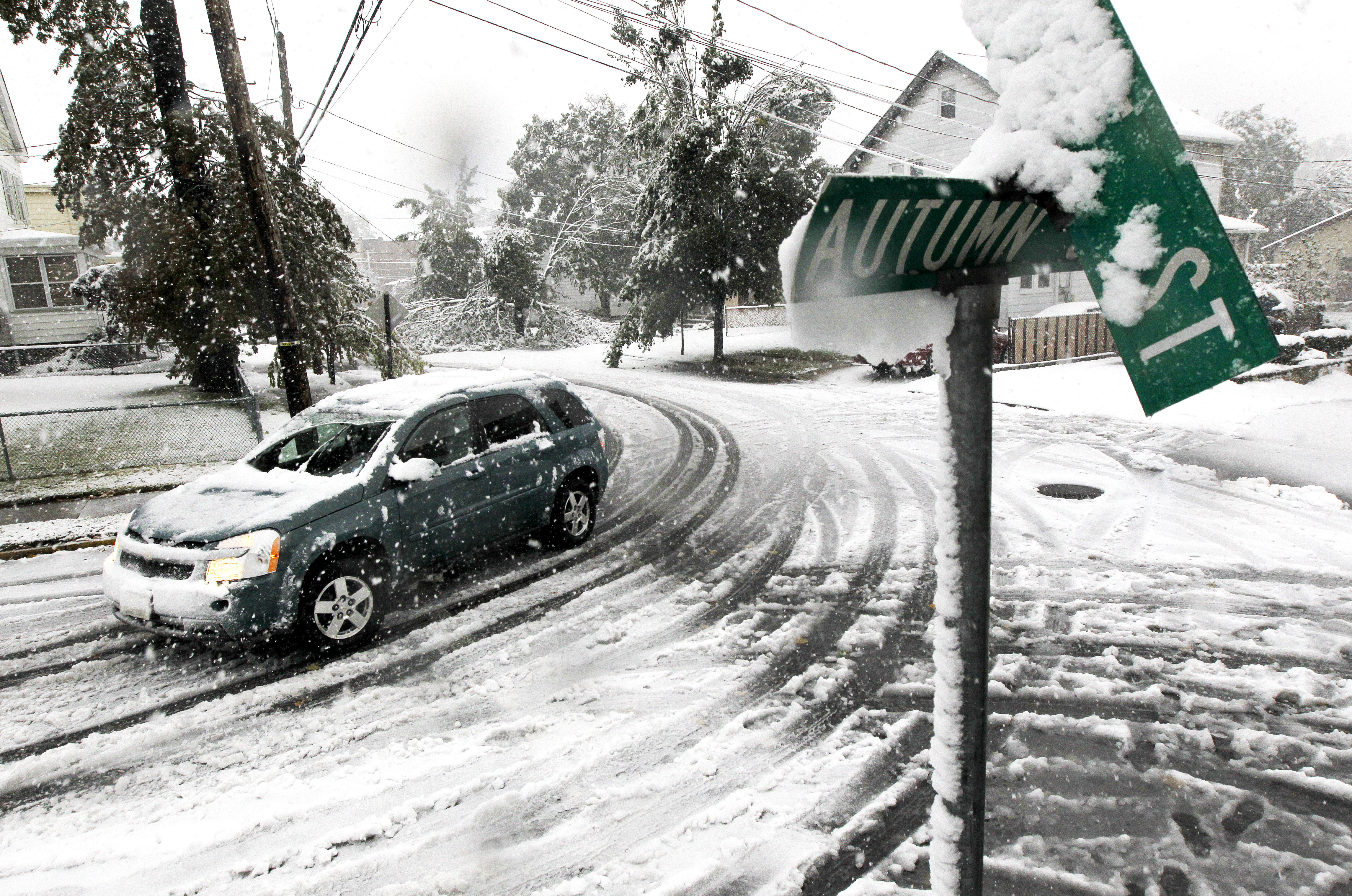 A vehicle makes its way at the snow-covered intersection of Autumn and Grove Streets in Lodi, N.J., following a rare October snowstorm that hit the region, Saturday, Oct. 29, 2011.