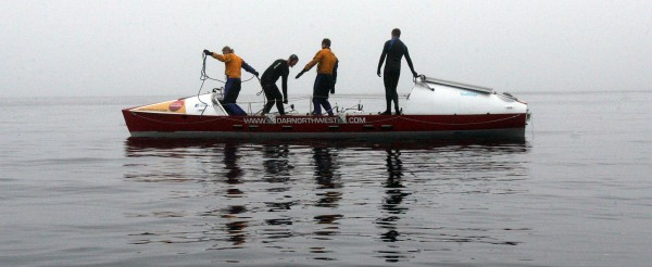 Four extreme rowers are preparing for a nonstop circumnavigation of Vancouver Island in this 29-foot boat. Jordan Hanssen (left to right), Adam Kreek, Greg Spooner and Richard Tarbill get ready for flip tests in Puget Sound.