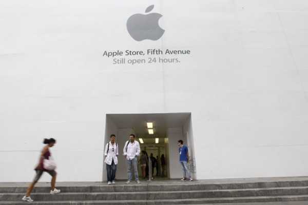 In this Aug. 25, 2011 photo, customers stand outside the Apple flagship store on Fifth Ave., in New York. Apple fans are amped. The computer and gadget maker is expected to announce a new, more powerful version of its wildly popular smartphone this week, more than a year after it unveiled the iPhone 4.