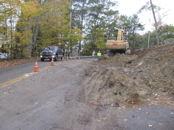 Where an excavator stands on Wednesday, October 19, 2011, used to be where a ledge jutted dangerously within inches of the travel lane on Route 128 in Woolwich. The ledge is being blasted away and removed by a contractor for the Maine Department of Transportation.